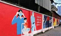 Hanói promueve la prevención y el control del covid-19 con murales de propaganda