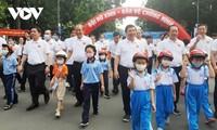 Deputi Harian PM Truong Hoa Binh berjalan kaki untuk menggerakkan seluruh rakyat memakaikan helm pada anak-anak