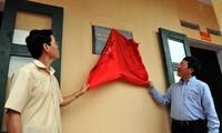 Deputi Perdana Menteri Pham Binh Minh memasang papan penyerahan sekolah kepada pelajar miskin