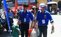Freiwillige Helfer in blauen Hemden bei der Hochschulaufnahmeprüfung