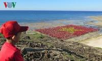 Record des chanteurs de l'hymne nationale formant le drapeau national sur la plage