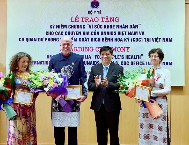 """Kementerian Kesehatan Vietnam memberikan lencana peringatan """"Demi kesehatan rakyat"""" kepada 3 pakar asing  - ảnh 1"""