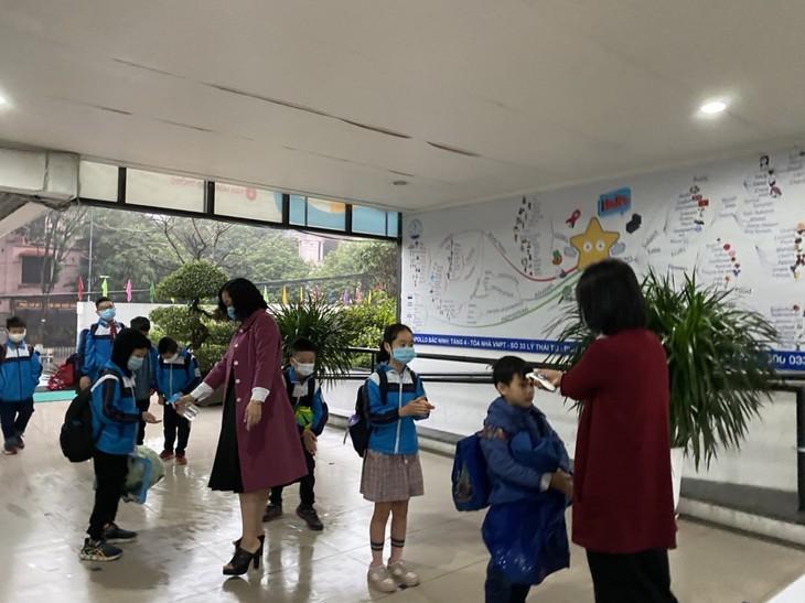 Los alumnos vietnamitas vuelven a la escuela con el cumplimiento de obligaciones antiepidémicas - ảnh 4