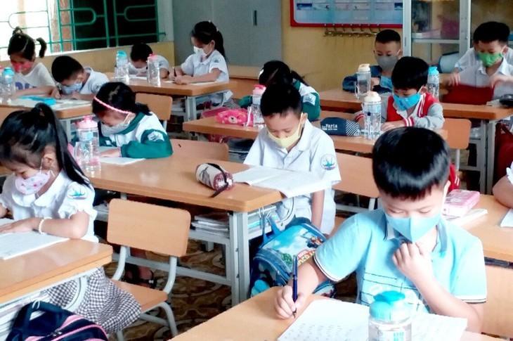 Los alumnos vietnamitas vuelven a la escuela con el cumplimiento de obligaciones antiepidémicas - ảnh 6