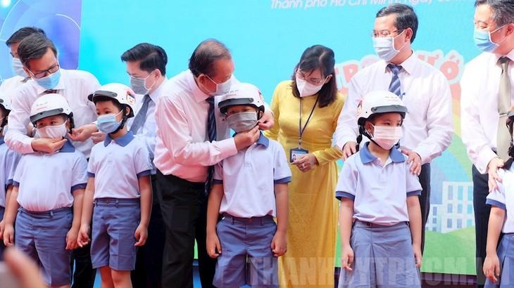 Вице-премьер Чыонг Хоа Бинь принял участие в церемонии открытия нового учебного года и вручил мотошлемы школьникам первого класса - ảnh 1
