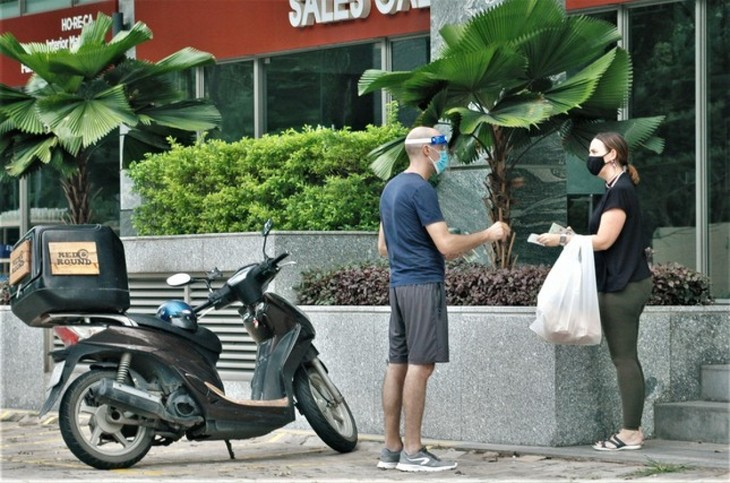 Foreigners follow social distancing rules in HCM City for COVID-19 fight - ảnh 9