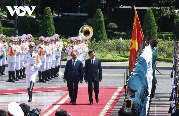Нгуен Суан Фук с супругой председательствовал на церемонии встречи генсека НРПЛ, президента ЛНДР, прибывшего во Вьетнам с официальным визитом - ảnh 1